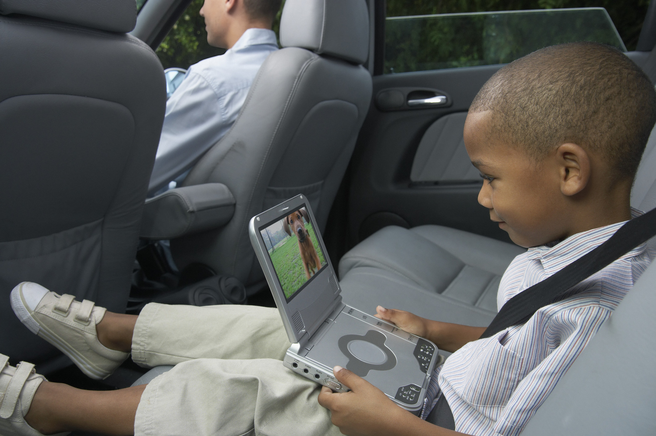 A kid sitting in the back of a car watching a video of a dog on a portable DVD player.