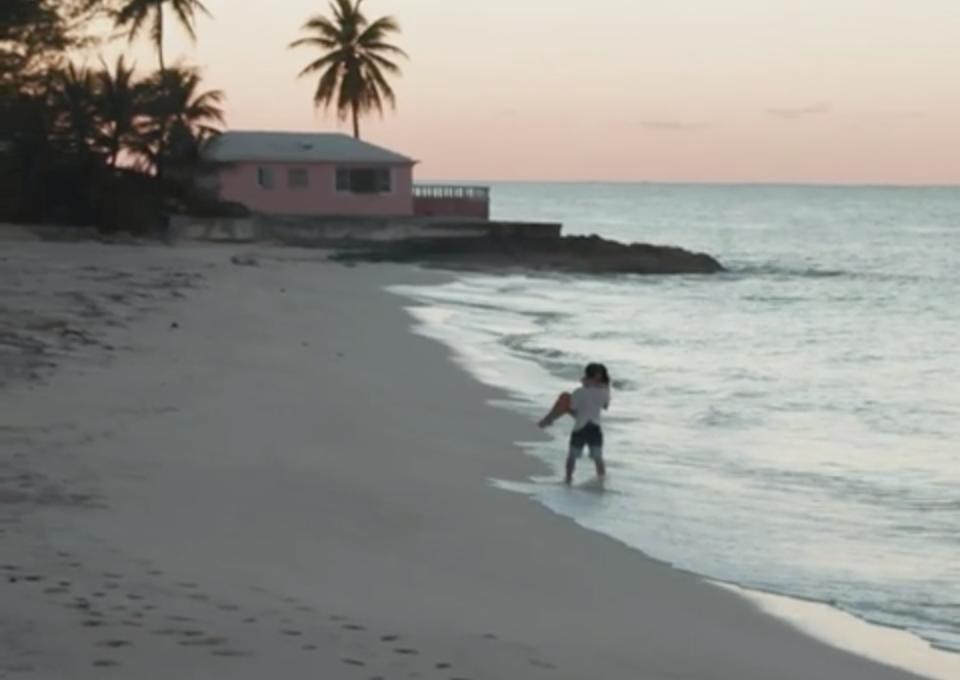 A man carries a woman along the beach at sundown