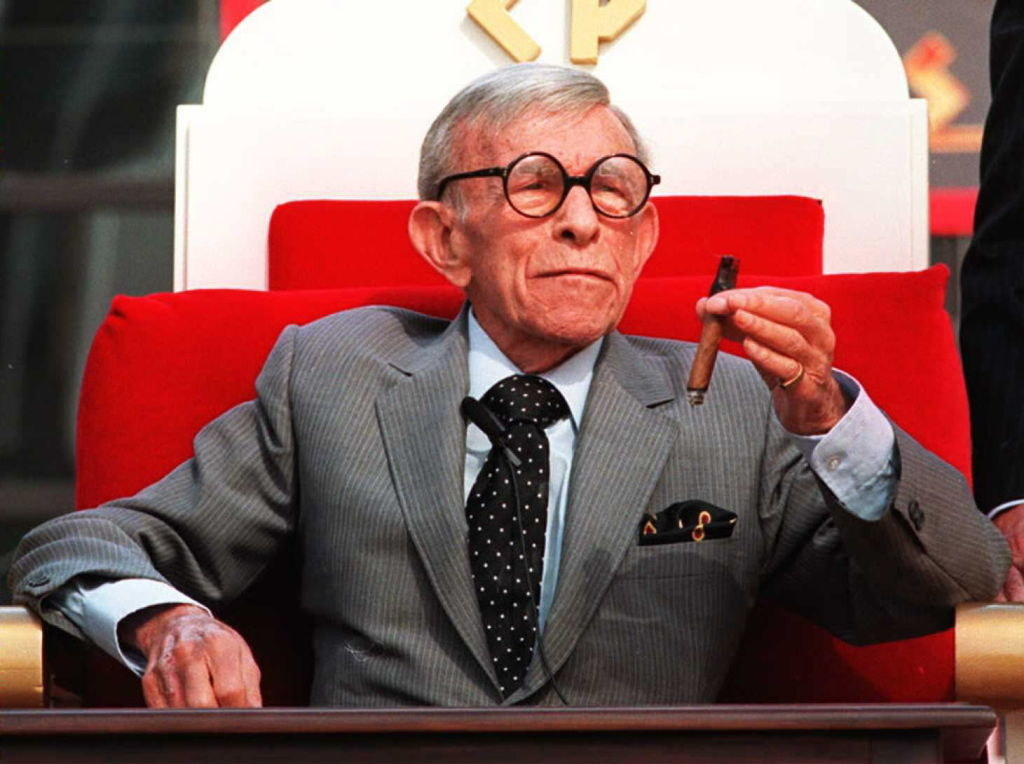 A nearly 100-year-old George Burns in a suit smoking a cigar