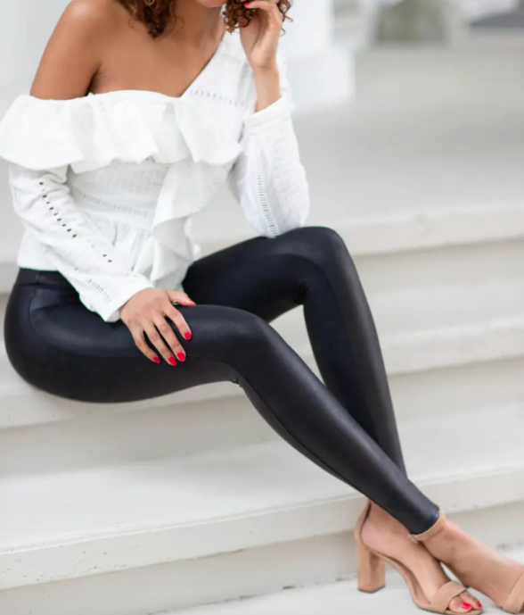 A model sitting in the Spanx faux leather leggings.