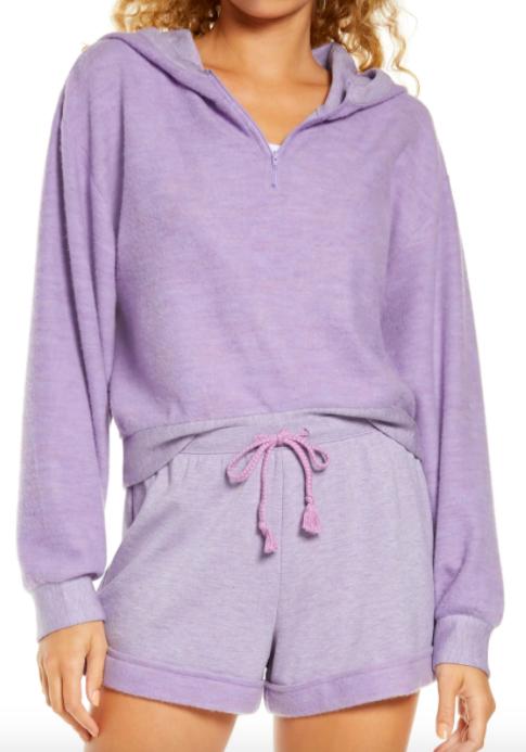 A model wearing the half-zip BP. fleece hoodie in purple sheer heather.