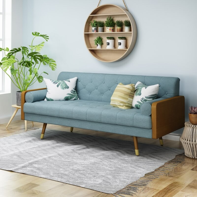 The teal sofa with wood accents on the legs and arms