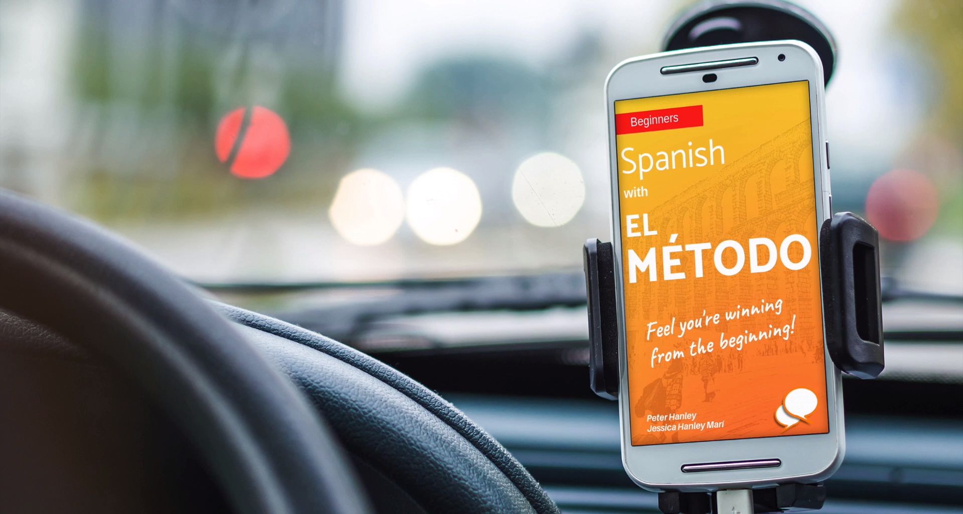 A phone placed in a phone mount on the dashboard of a car There is a Spanish language app open on the screen
