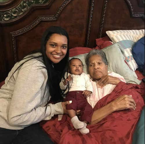 Caitlyn Lewis and her grandmother, Rose Lewis, hold a baby while on a bed.