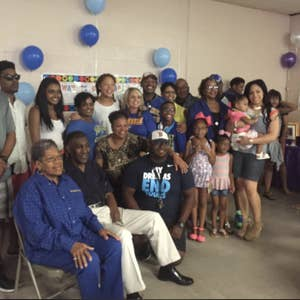 The Lewis family, seated and standing together, pose for a family photo at a party with blue balloons.