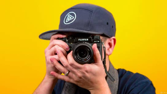 A person holds a camera to their face