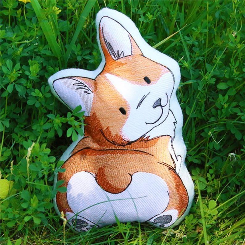 A pillow in the grass of a cartoon looking corgi