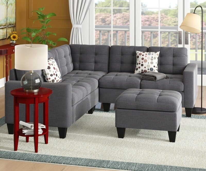 The grey tufted symmetrical sectional with a matching ottoman