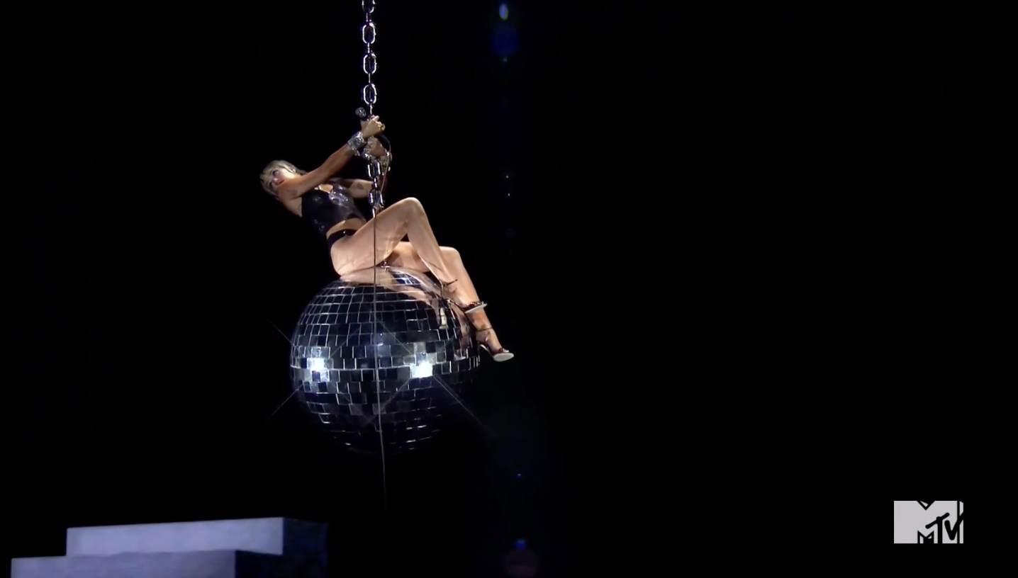 """Miley on top of a giant disco ball in the same pose as her original """"Wrecking Ball"""" video"""