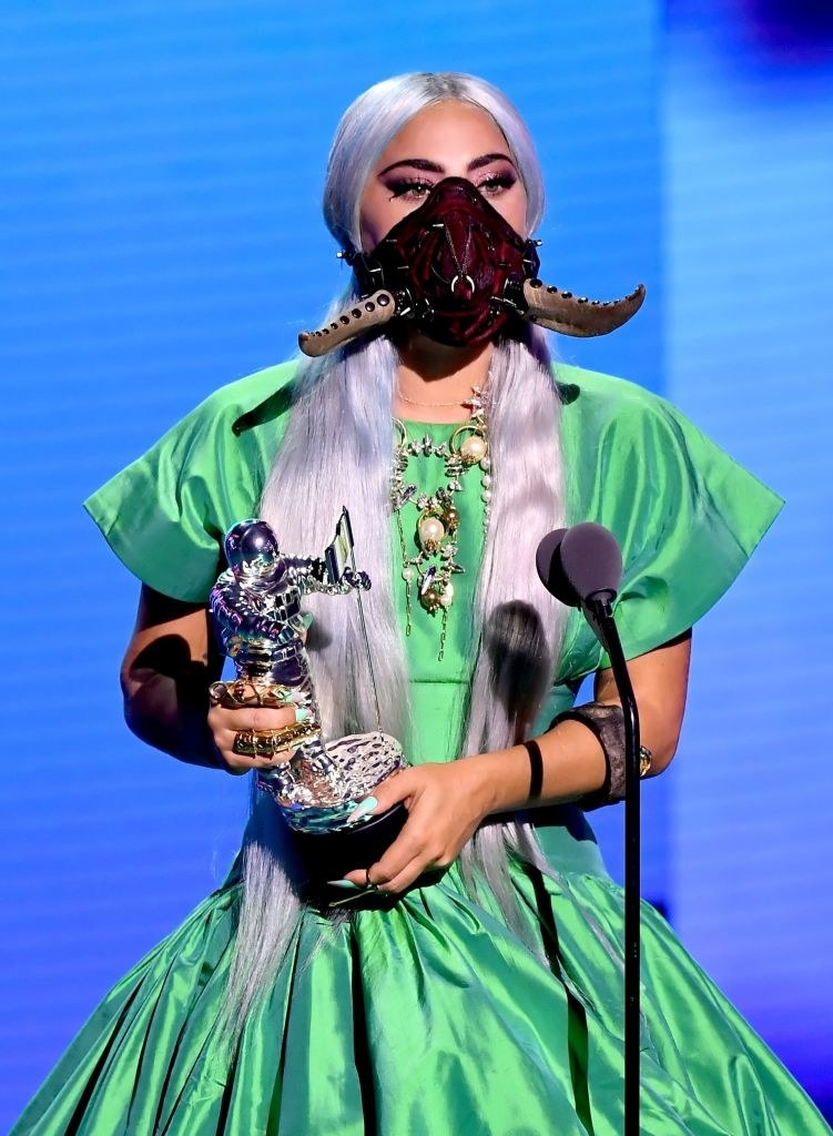 Lady Gaga wearing face mask with studded tusks and shiny dress while holding award