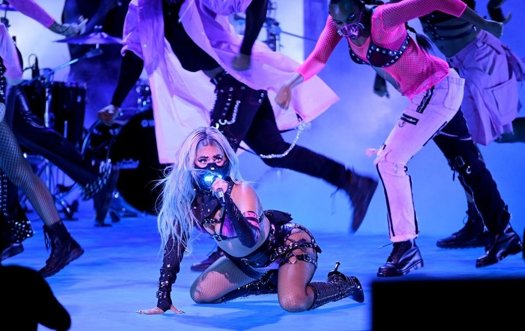 Gaga performing on her knees with a microphone