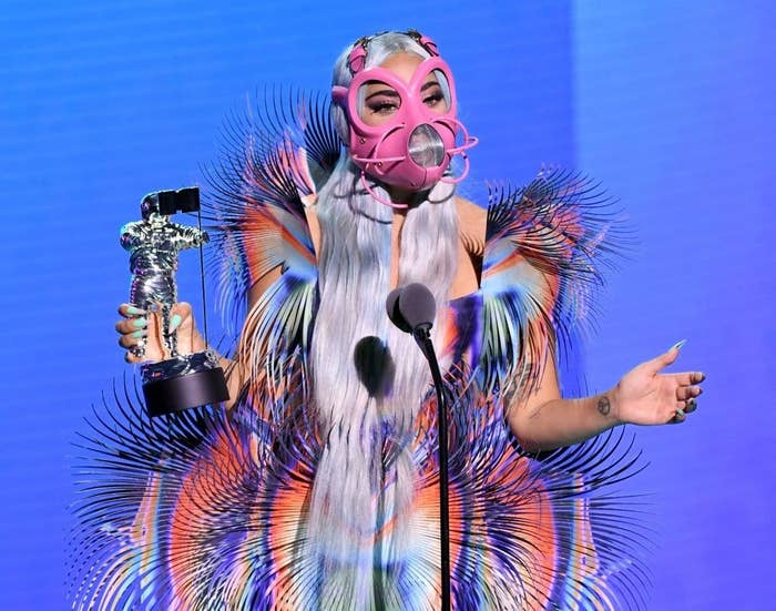 Lady Gaga in pink face mask and rainbow-colored outfit holding silver award
