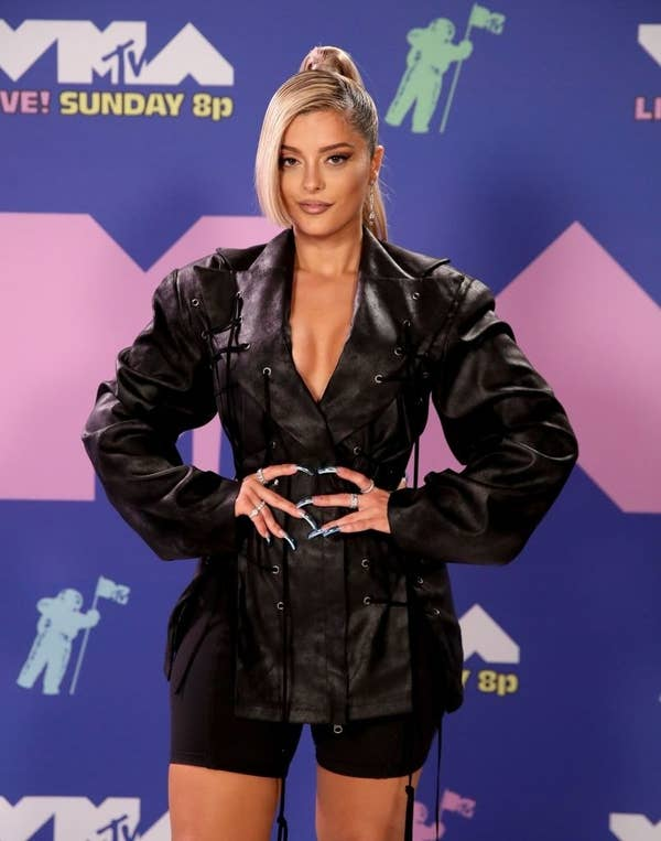 Bebe Rexha posed in a leather jacket dress