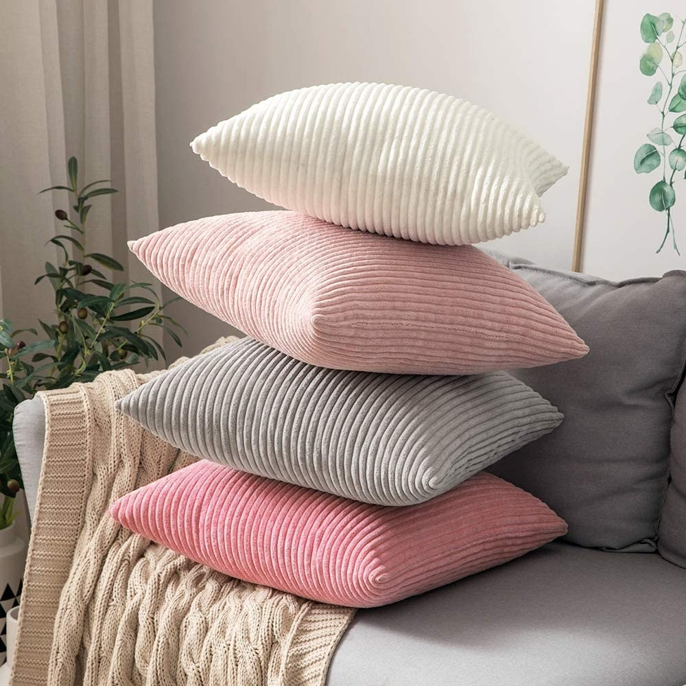 Four pillows with corduroy pillowcases on them stacked on a sofa