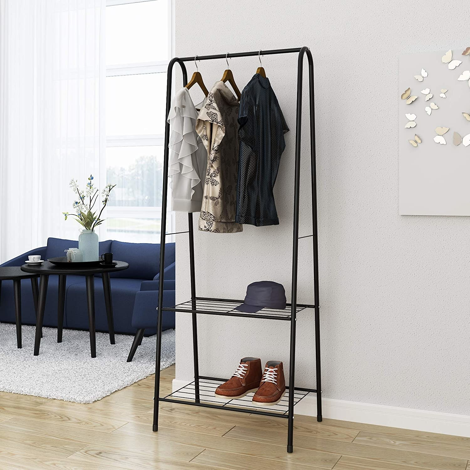 The clothing rack with three shirts, a hat, and a pair of shoes on it