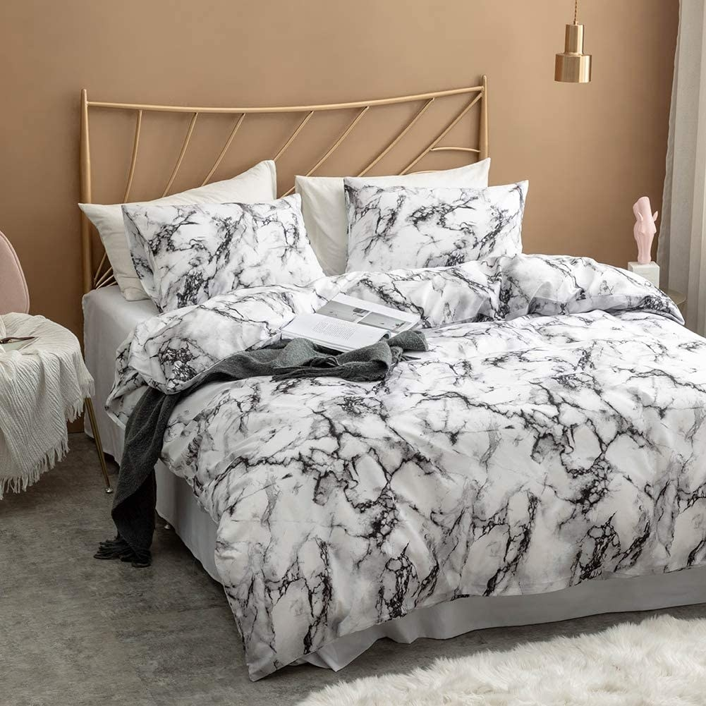 A bed with the marble duvet cover and shams on it