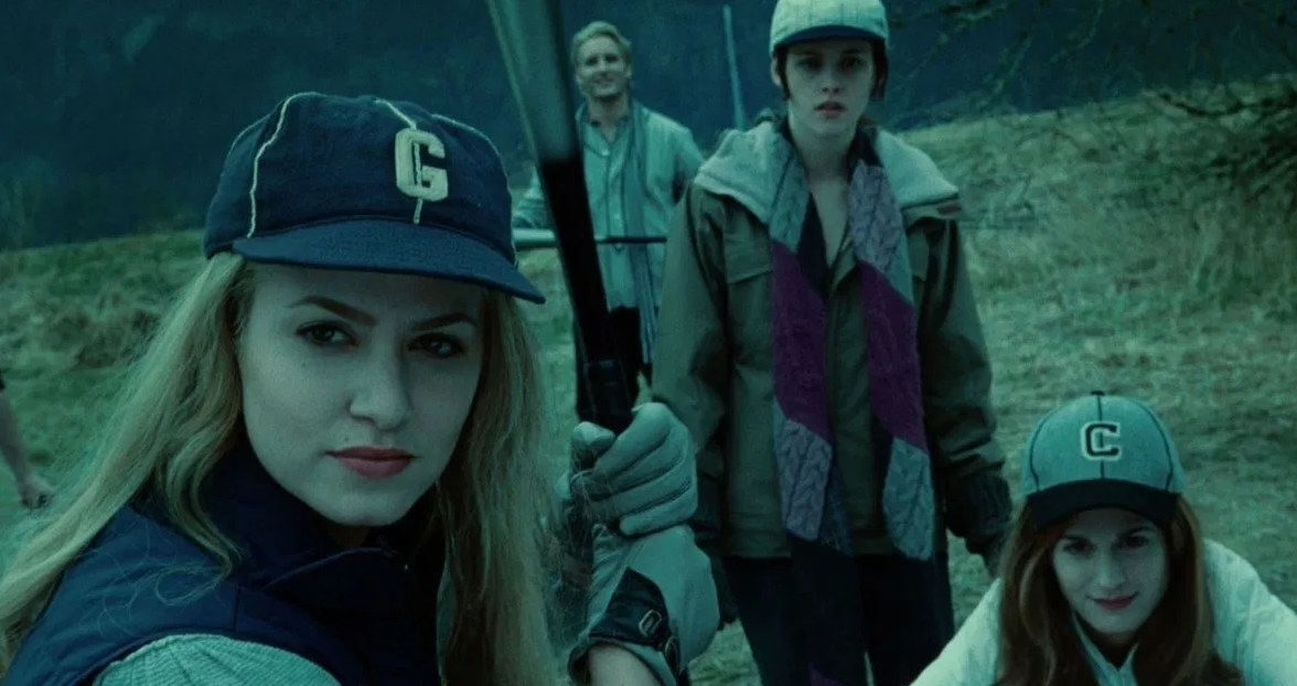 Still from Twilight: Rosalie holds up a baseball bat while Esme crouches behind her, Bella stands behind Esme, and Carlisle stands in the background
