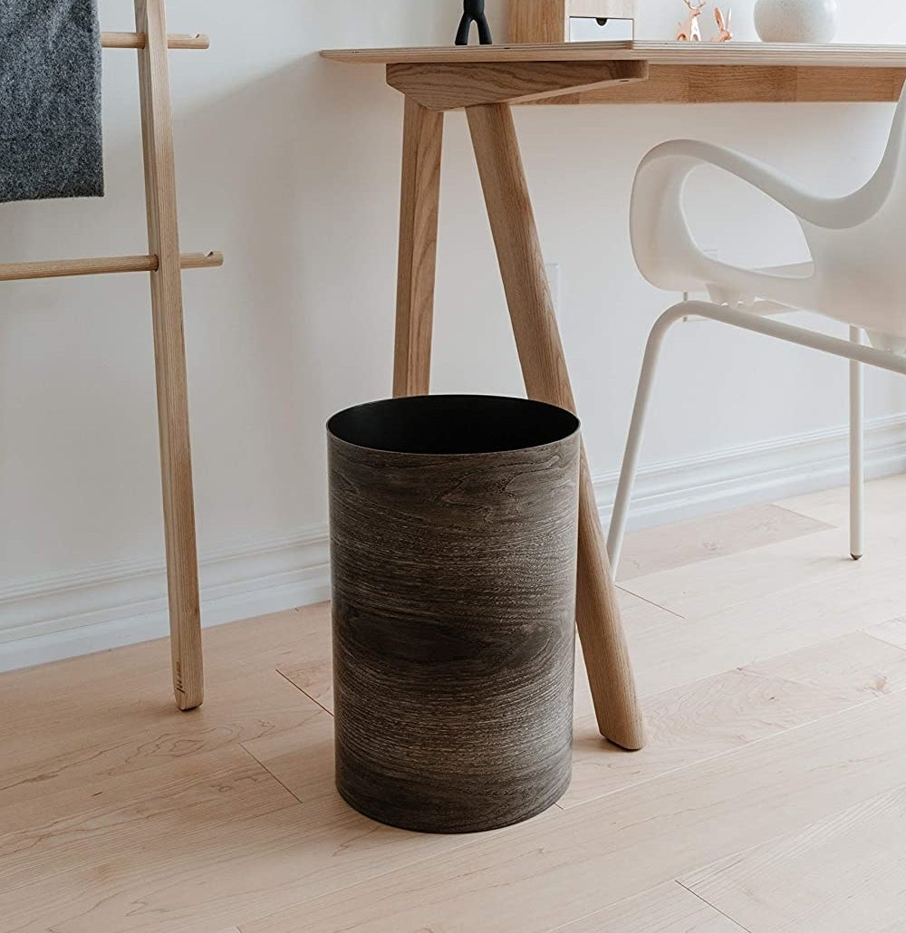 The faux wood trash can next to a desk