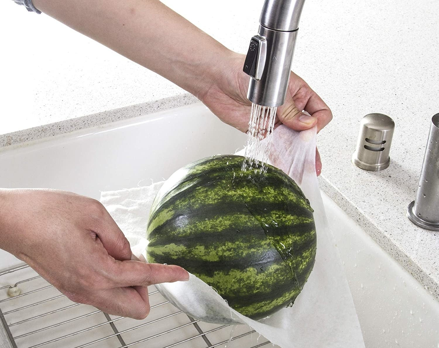 Model's hands cleaning a watermelon held by a single bamboo towel