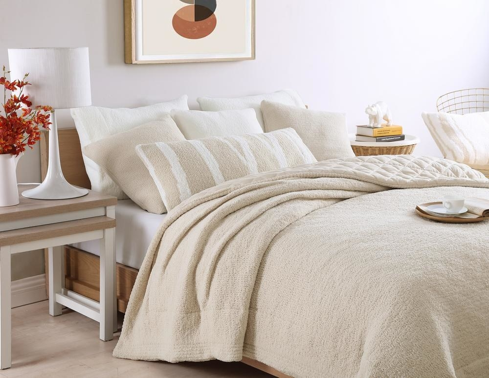 A Sahara tan-colored comforter partially folded down on a bed