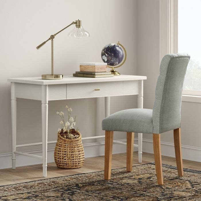 The white Threshold Cambridge Wood Writing Desk with Drawers in a display office