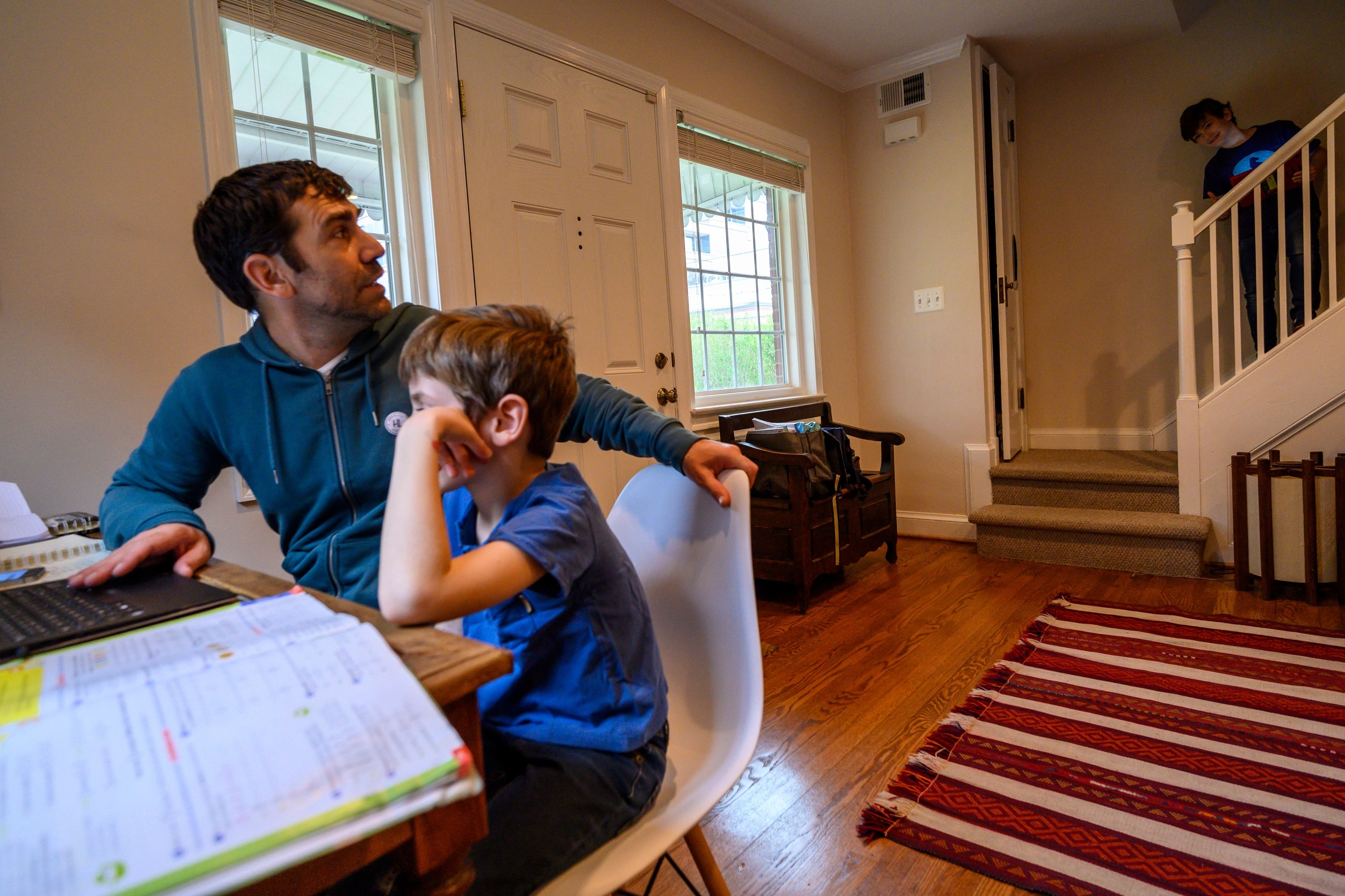 A dad homeschooling his young son.