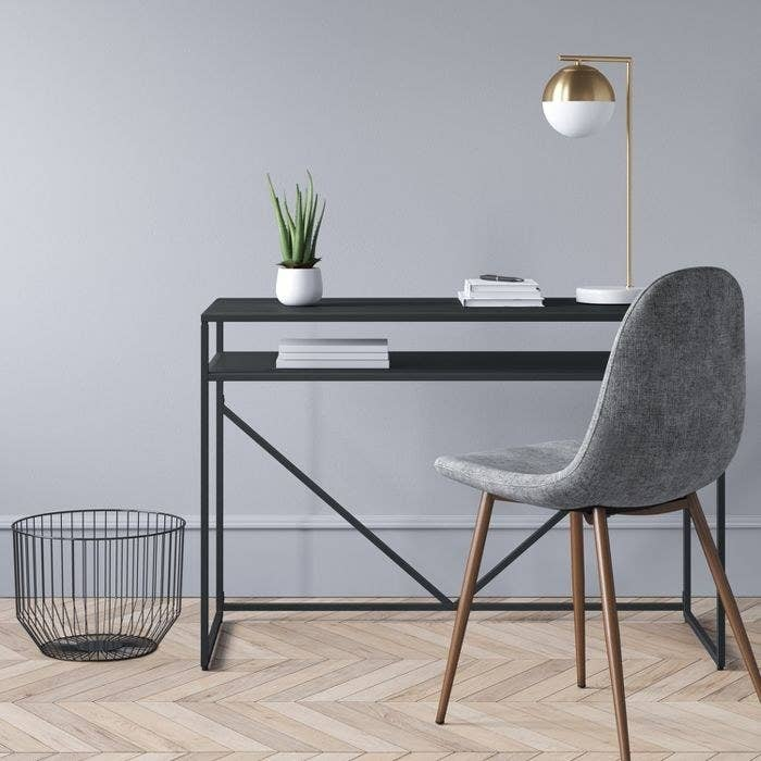 The black Project 62 Glasgow Metal Writing Desk with Storage in a display office