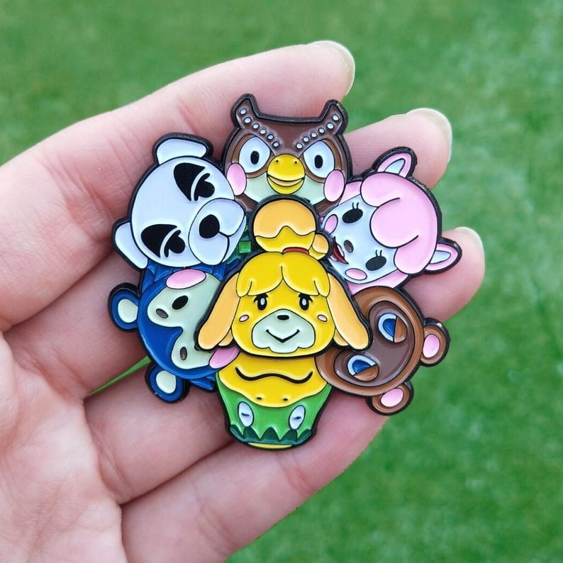Hand holding a large colorful pin featuring seven Animal Crossing characters