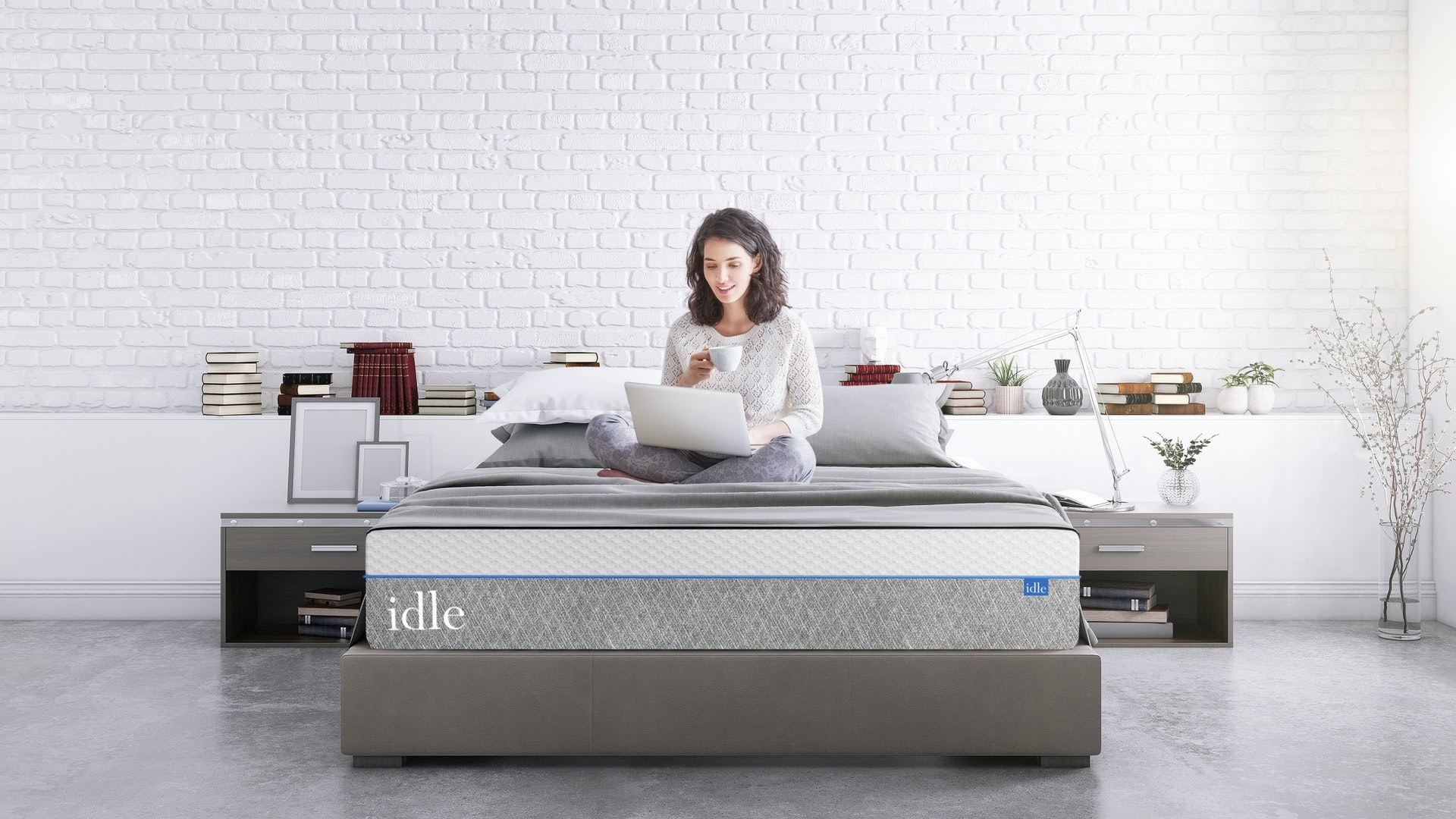 Model working on their laptop sitting on an Idle Sleep Plush mattress