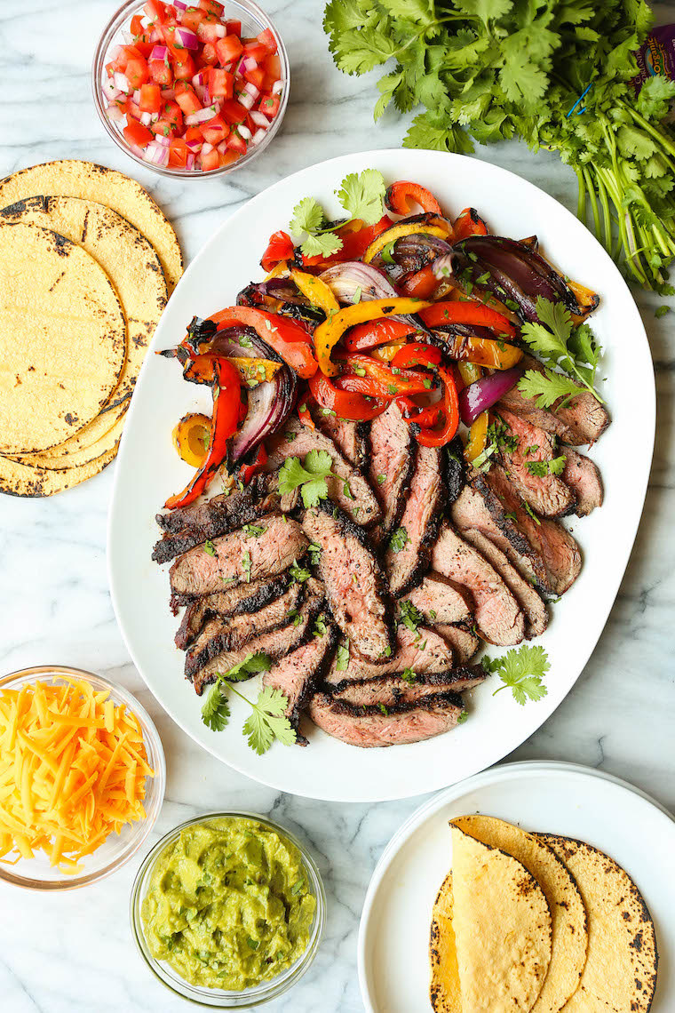 Fajitas served family style with bowls of cheese, guacamole, tortillas, and a big plate of grilled steak with peppers and onions.