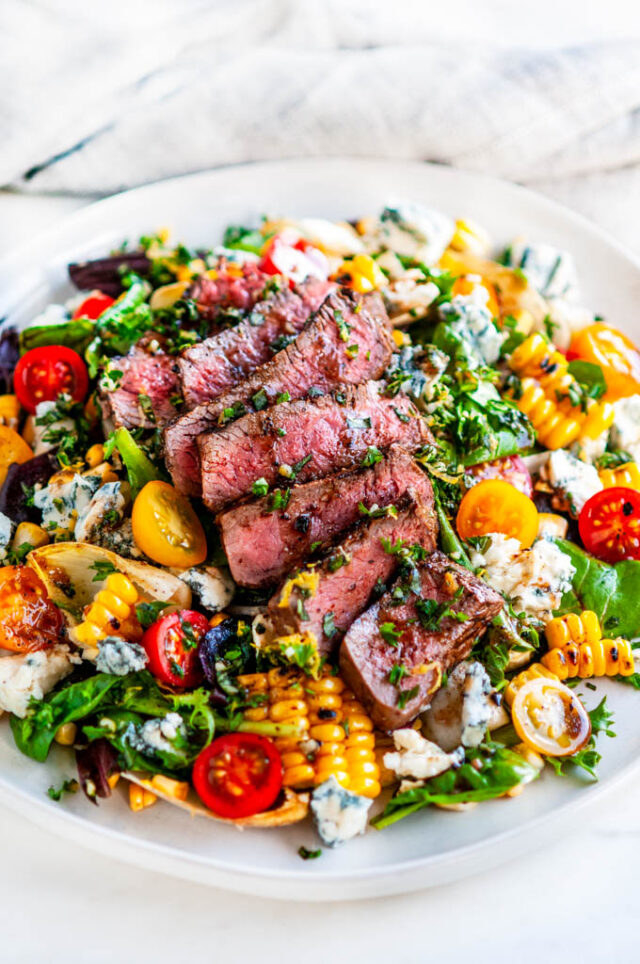 A salad topped with gorgonzola chunks, cherry tomato halves, corn off the cob, and slices of steak over lettuce.