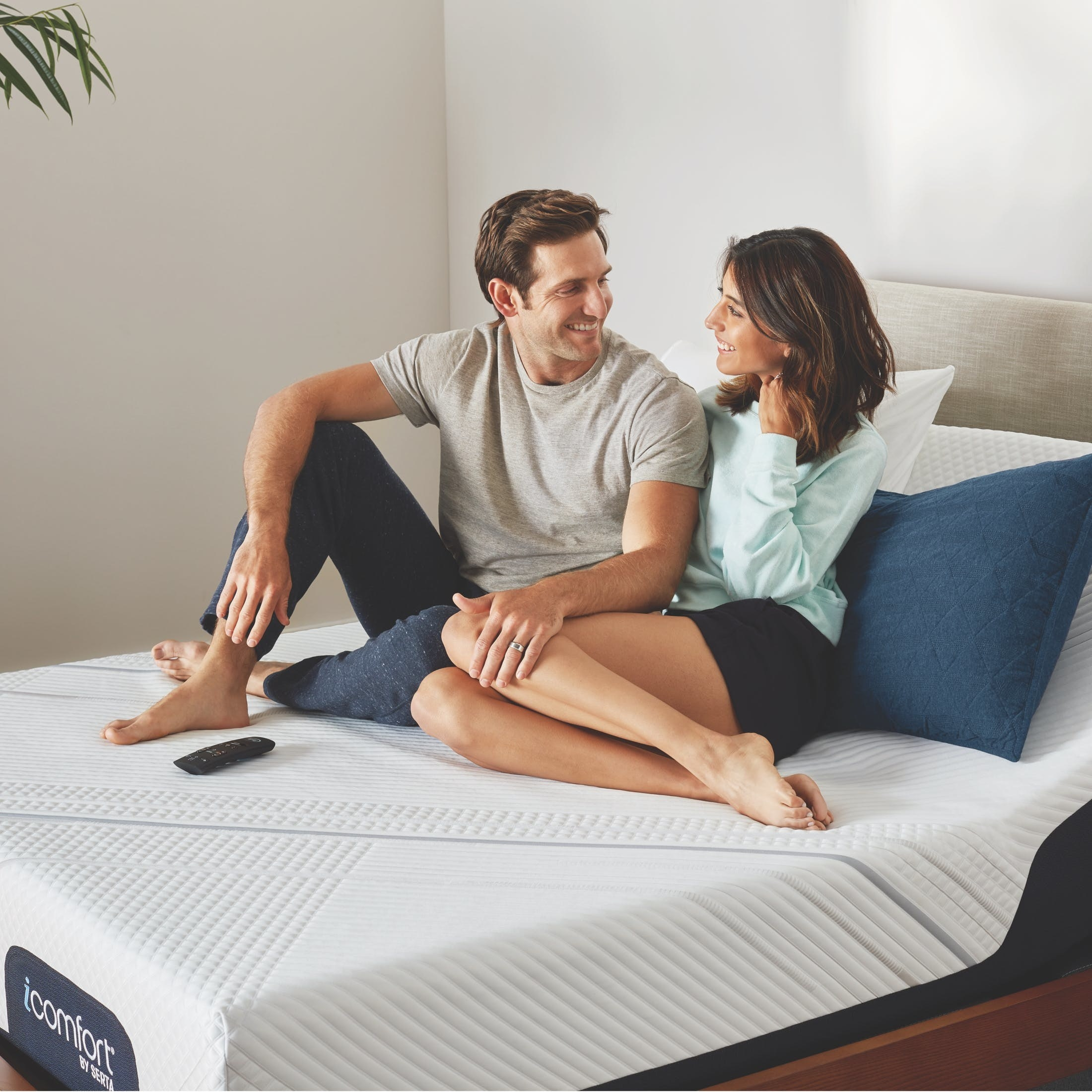 A couple sitting on an iComfort mattress