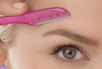 Model using tool to shave hair above the eyebrow