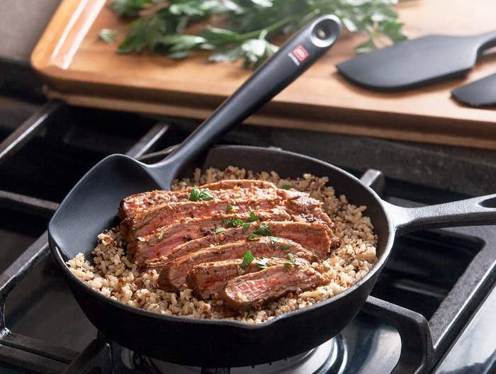 black spatula with rounded edges in a cast iron pan with grains and steak