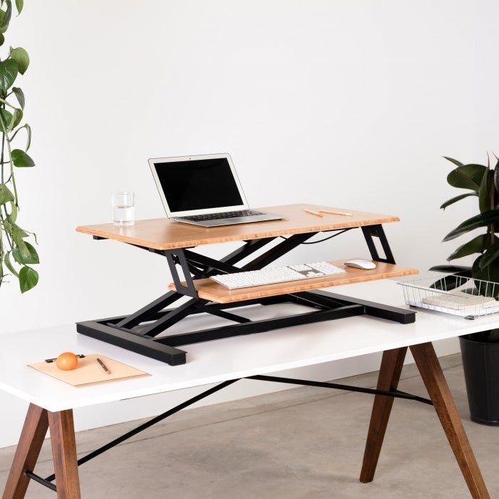 A two-tier standing desk in light brown and black on top of an actual desk with a laptop and keyboard on it