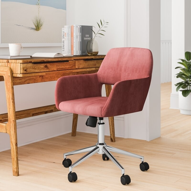 Pink velvet office chair with a rectangle opening in the back and five silver legs with black wheels