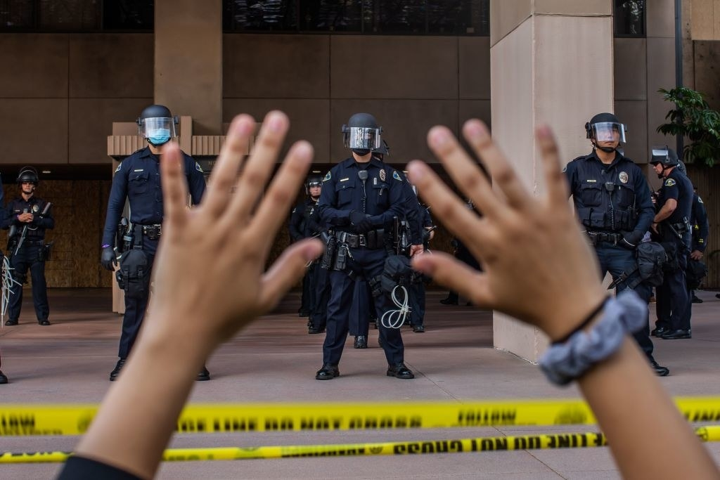 Protestor with their hands up in front of police