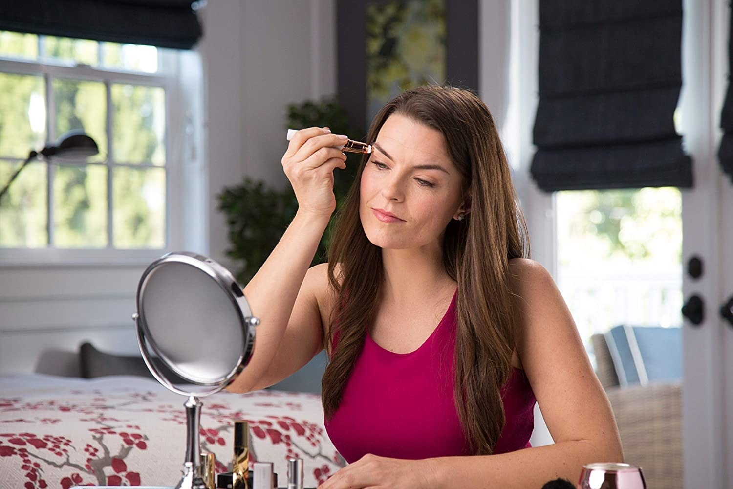 A person using the Flawless Eyebrows gadget to clean up their eyebrows