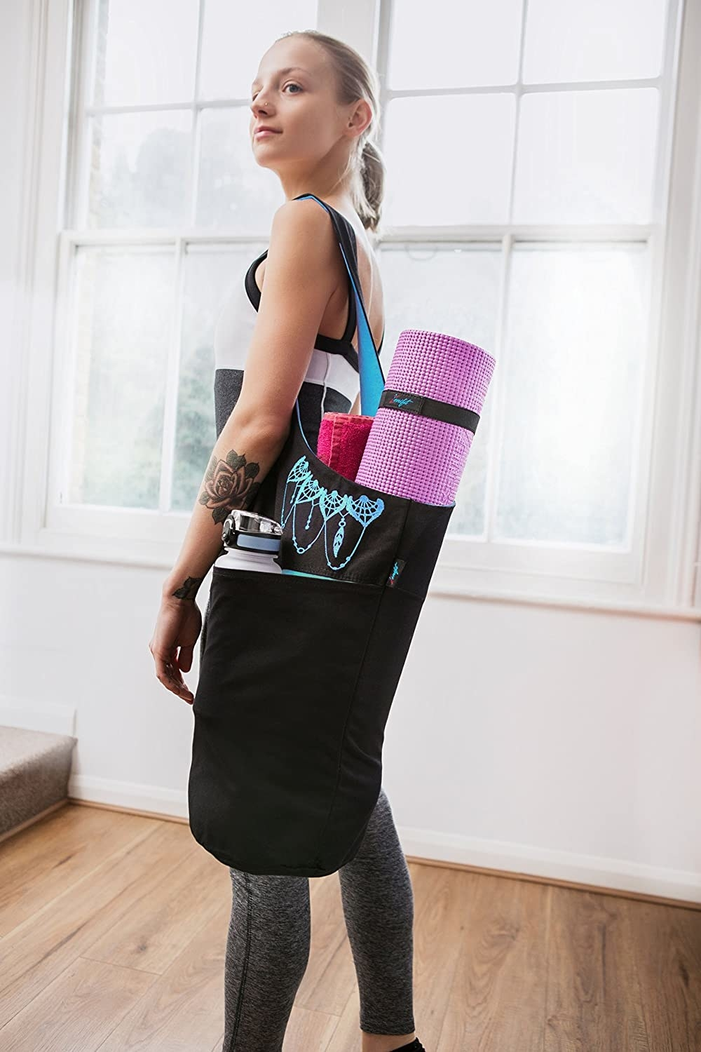 A person carrying their yoga mat in the mat bag