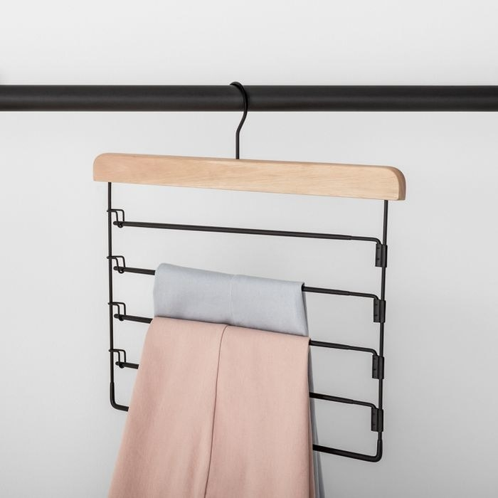black pants hanger holding up a pink pant and a light gray pant