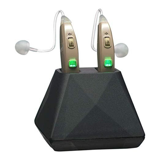 The gold hearing aids in a black charging stand