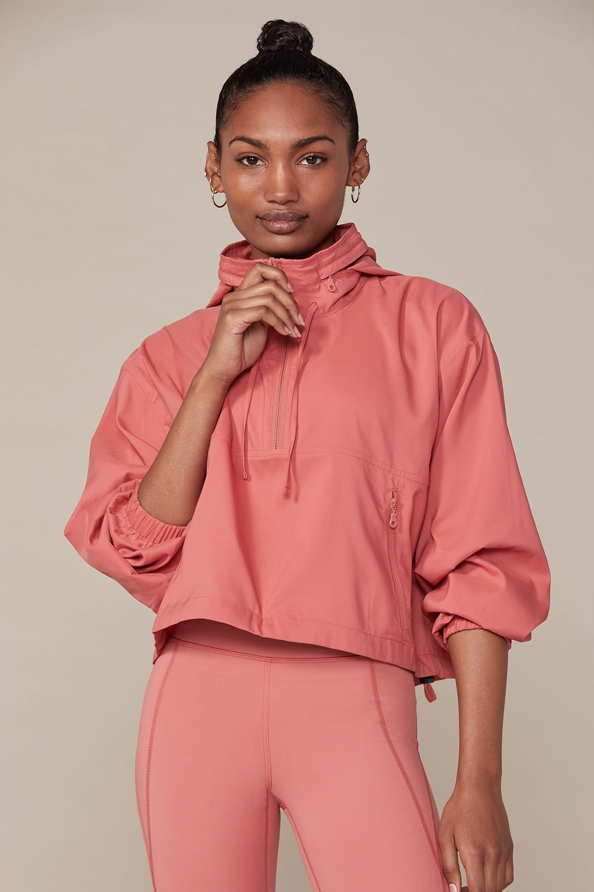 Model wearing a clay-colored half zip windbreaker