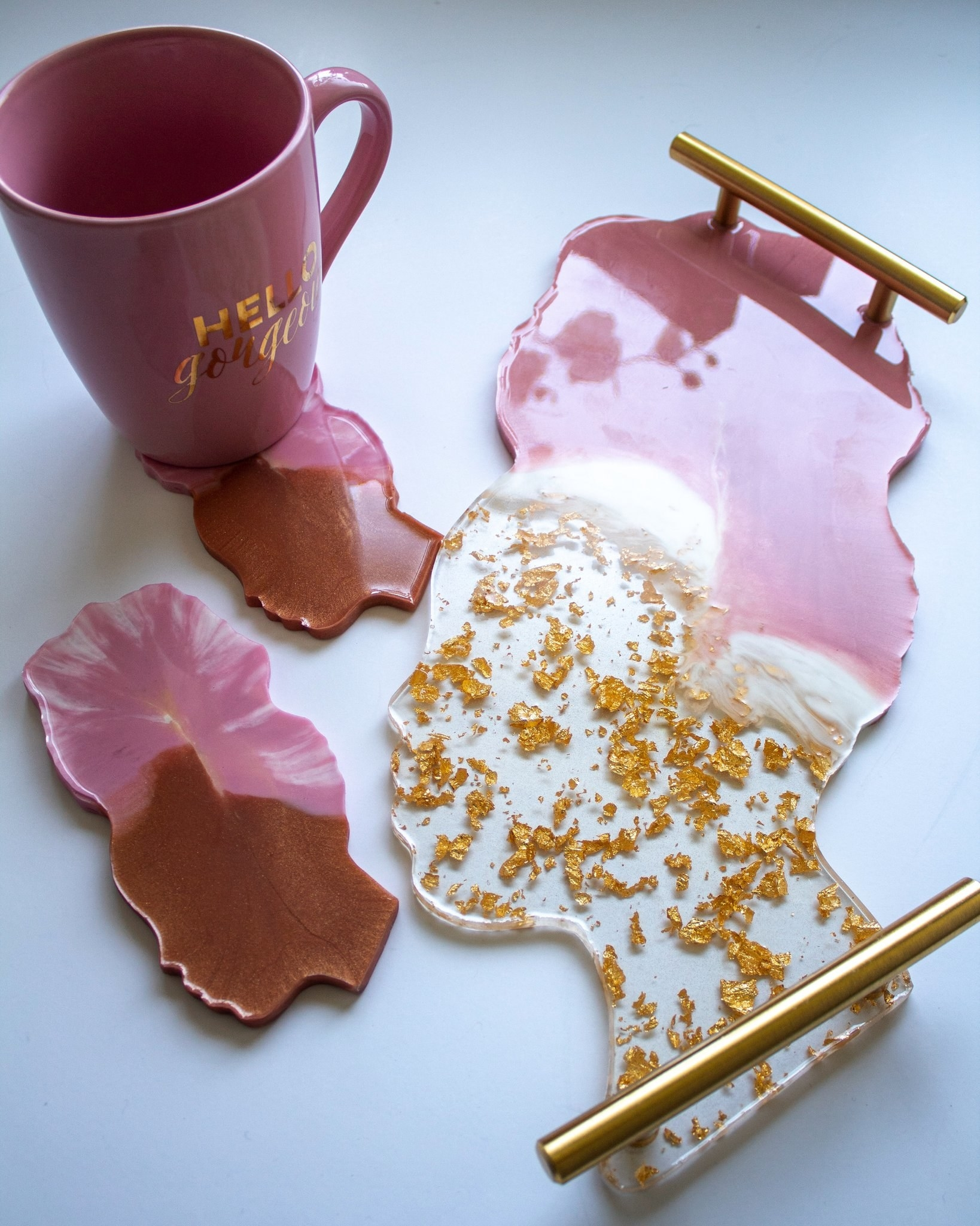 Tray with gold handles and coasters in pink and gold resin, featuring a shape that resembles the side profile of a person wearing a turban