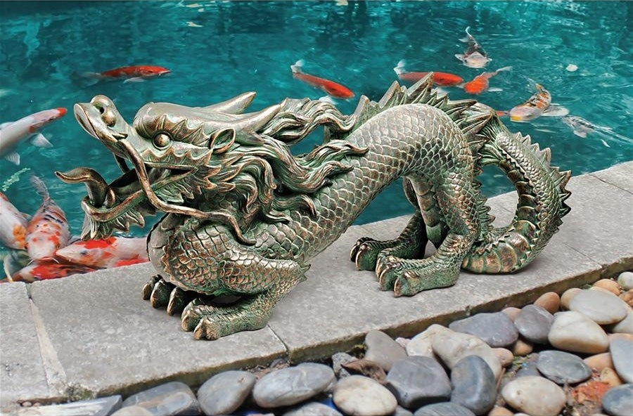 The green and gold dragon statue, in front of a koi pond