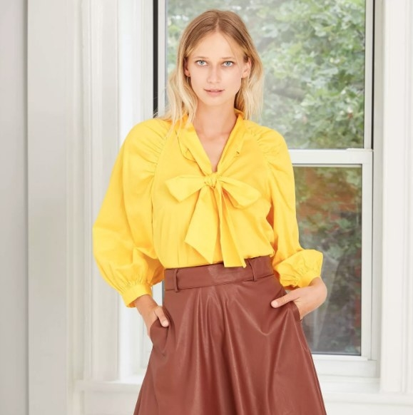Model in the bright yellow blouse with bow tie