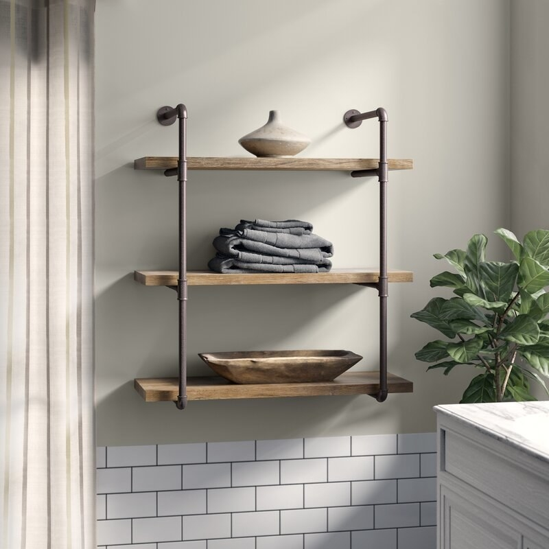 The three-shelf unit displayed in bathroom holds towels and decor