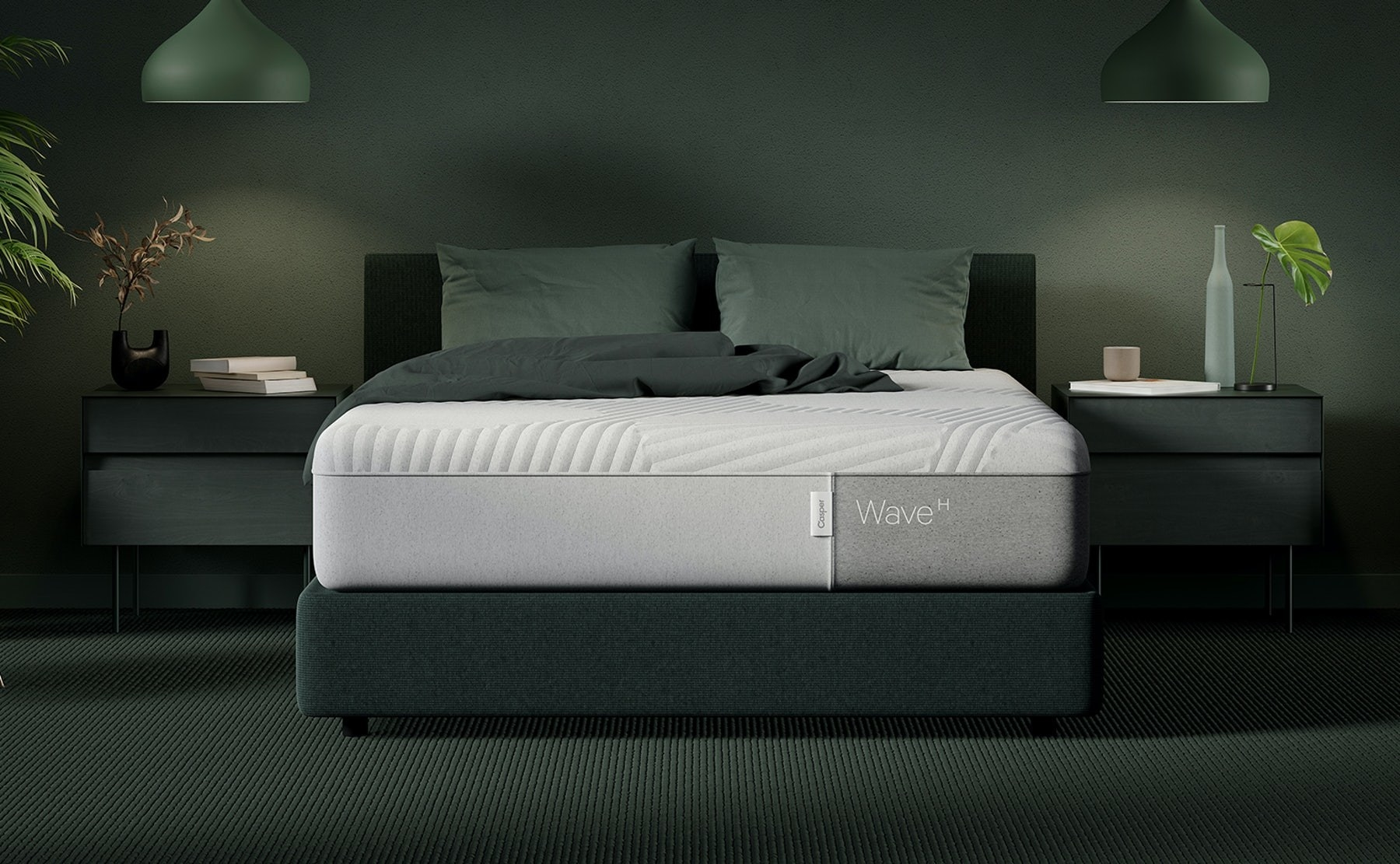 A white Casper mattress on a green bed frame