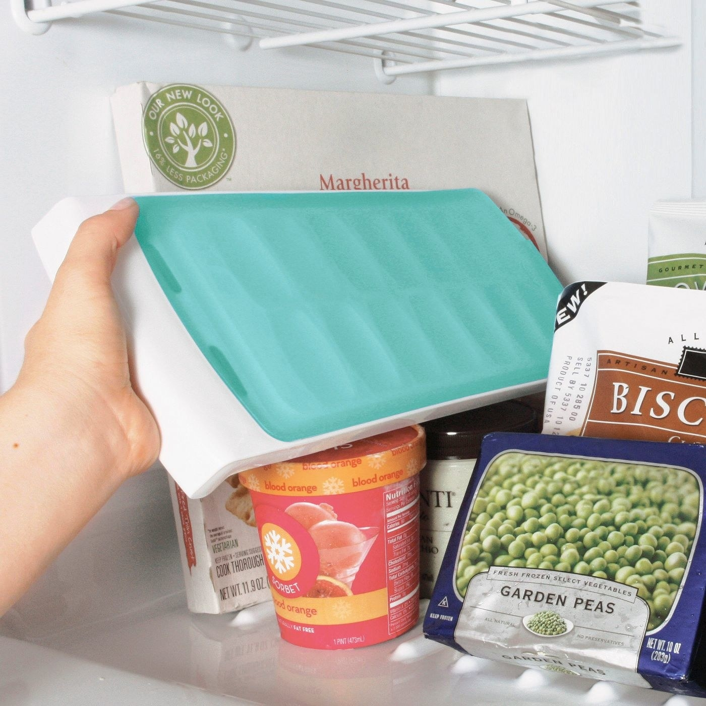 person placing no spill ice cube tray vertically in a freezer