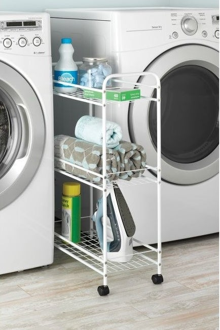 white rolling cart in between a washer and dryer with laundry supplies on it