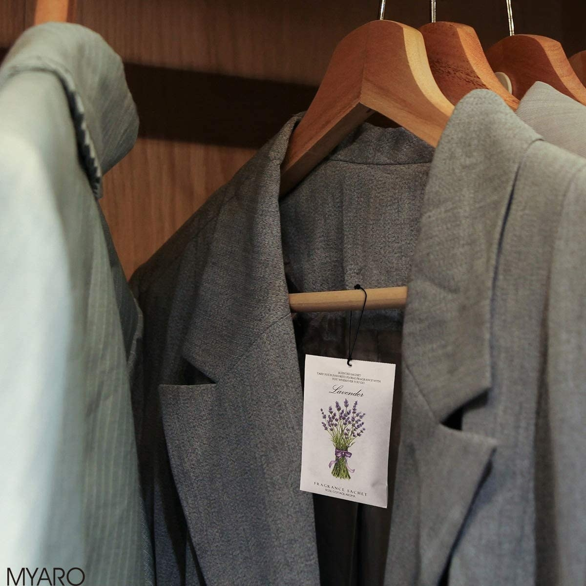 A lavender sachet hangs in a coat that's hung in a closet